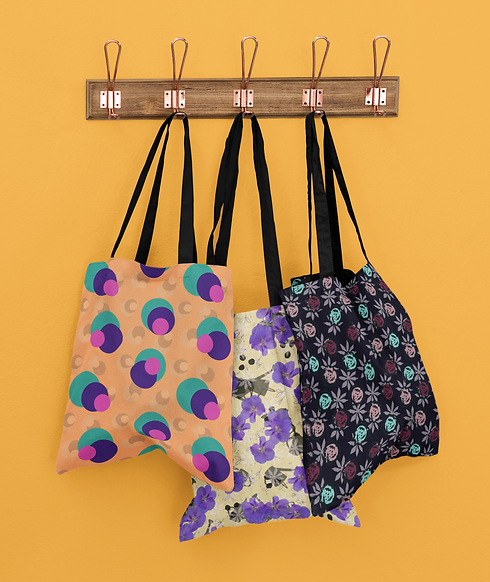 mockup-of-three-customizable-tote-bags-hanging-against-a-solid-color-wall-41717-r-el2.png