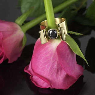 Gold and black sapphire ring on a rose