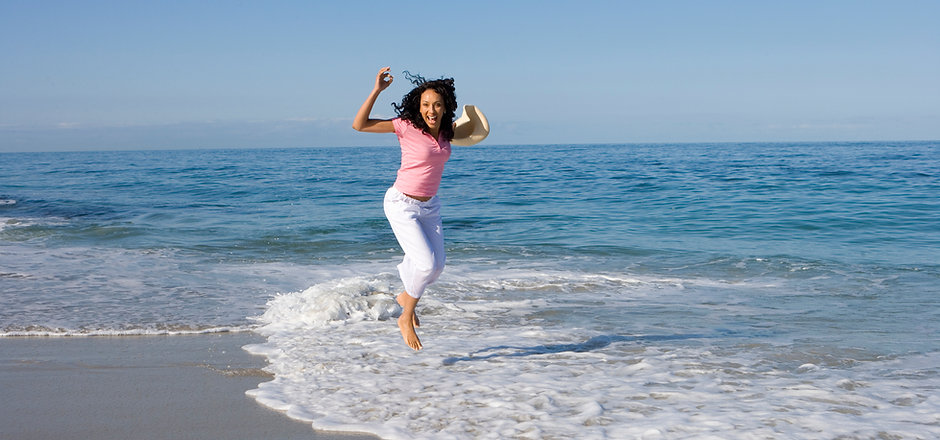 Woman jumping in waves on beach on summe