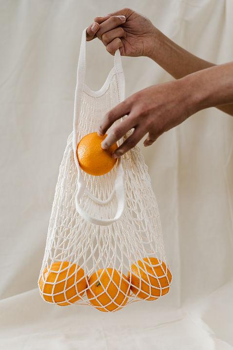 person-holding-orange-fruits-in-white-ne
