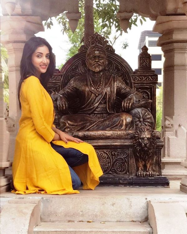 Rupali Bhosale Sitting In Front Of A Statue Of Shivaji