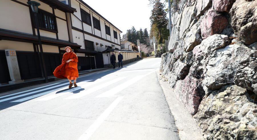 A buddhist monk in traditional orange robes, walking down a street in Koyasan, Japan