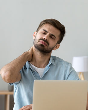 Millennial stressed man having neck and shoulder pain