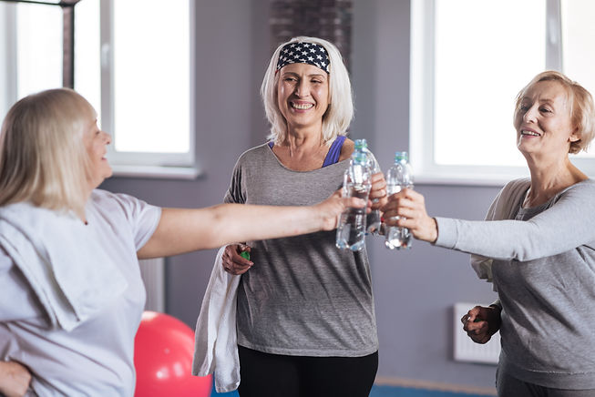 Joyful happy women holding bottles with