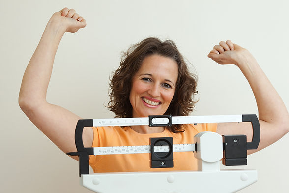 Mature woman celebrating weight loss on a medical weight scale..jpg