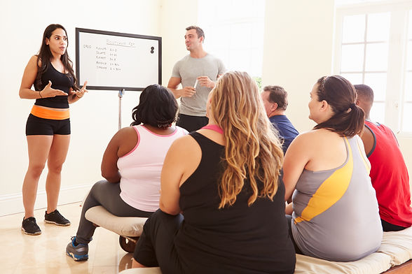 Fitness Instructor Addressing Overweight People At Diet Club.jpg