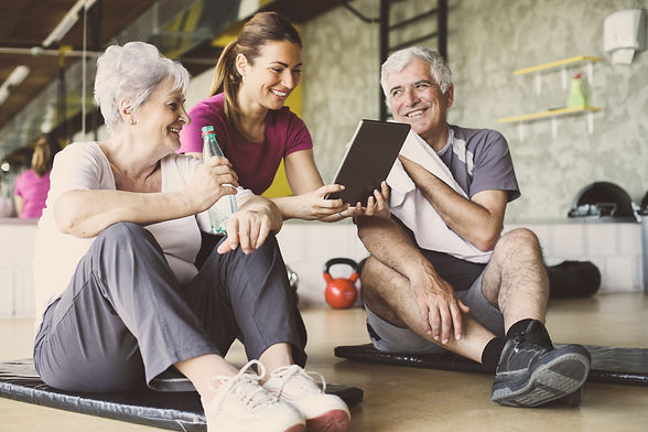 Senior couple in rehabilitation center. Personal trainer showing something on digital tabl