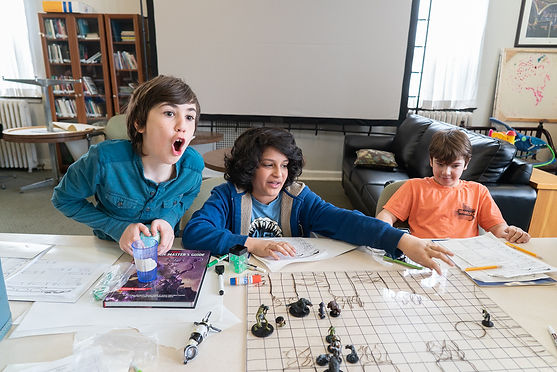 3 young boys are playing D&D. The left most boy is mid shout. The middle boy is reaching for something on the grid map. A third boy sits and watches. There is books and dice and paper scattered all over the table around the map.