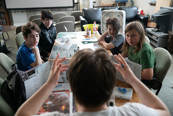 Looking over the head of a young dungeon master, 4 players look and listen intently. D&D books, dice, and pages are scattered around a grid map laden with figures.