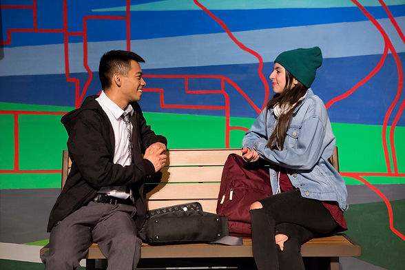 John (Aldrin Bundoc) and Jane (Margarita Valderrama) look at eachother and smile. They are sitting at a bus stop bench and a mural of red lines streaking across blue and green like a transit map is behind them.