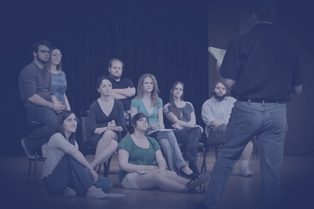 A stock photo of a drama class. A group of students listen to a teacher.