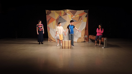 """""""La Maleta (The Suitcase)"""" performance, Jill Harland as Grandmother, Sofía Rodríguez as Roca, Oscar Moreno as Paz and Jessica Esmeralda Zepeda as Kadin. Roca and Paz hold hands in center stage as Grandmother stands to the left and Kadin sits to the right."""
