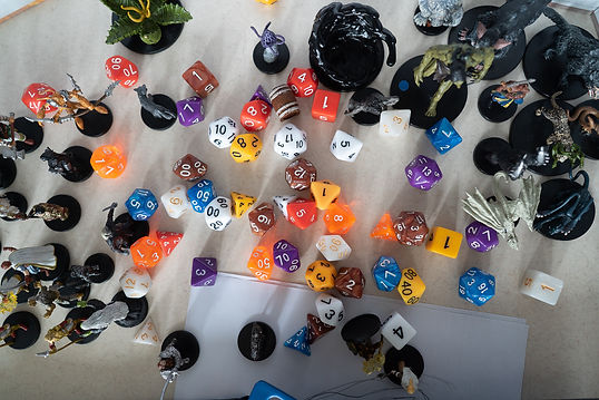 RPG Dice scattered on a table. Small figures of monsters on the sides of the image.