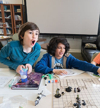 """Two young boys react mid game of Dungeons and Dragons. The left boy is white with long brown hair and is mid """"OOO"""" to the right is a boy with brown skin and large wavy brown hair, looking to the right."""