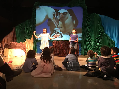 Birds of a Feather actors Bria McLaughlin and Michaela Di Cesare talk in front a group of children after a performance for a Q&A period. They are standing with the set behind them.
