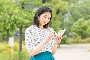 公園でスマートフォンを使用している女性