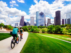 Riding Bikes in Houston Park (view of river and skyline of downtown Houston)