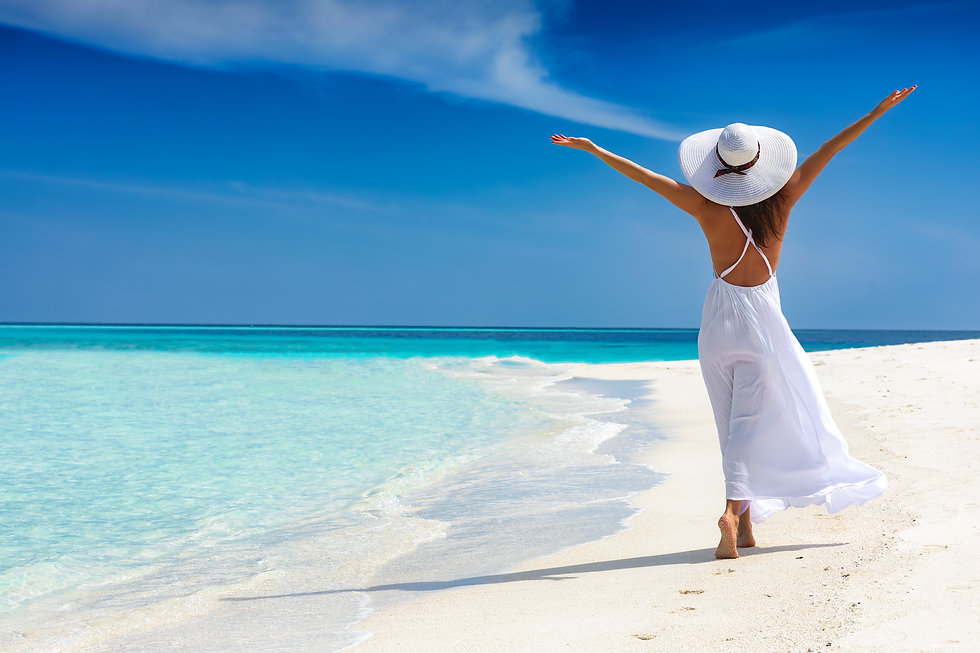 Happy traveller woman in white dress enjoys her tropical beach vacation.jpg