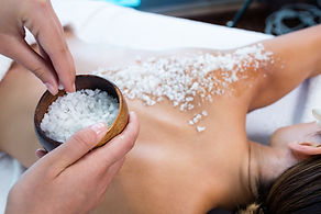 Woman enjoying a salt scrub massage at s