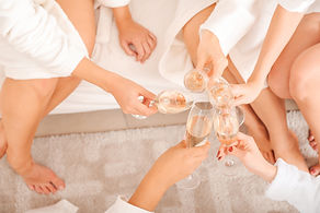 Happy young women drinking champagne at