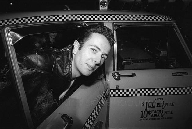The Clash arrive at JFK - Mick Jones, Joe Strummer, Paul Simenon. Joe Strummer getting out of a taxi.