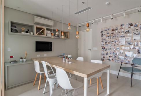 Sala de reunião com mural de fotos dos projetos.