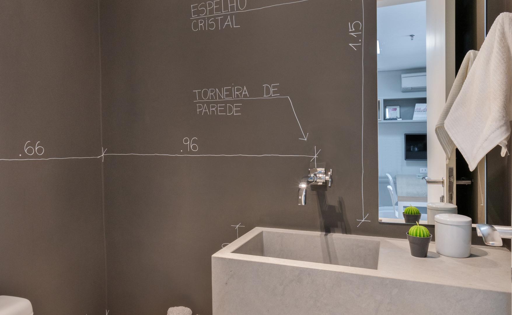 Lavabo com cuba esculpida e desenhos nas paredes.
