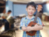 Asian boy with ukulele at music school.j