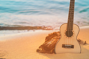 Guitar ukulele on sand beach with clear