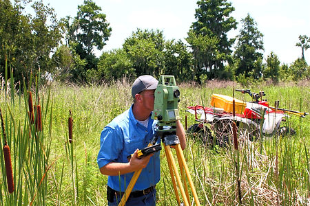 One of CivilSurv's survey crew members is using a total station, analyzing the slope between its stationary point and another specific point. Total Stations measure horizontal angles, vertical angles, and distance. CivilSurv's crew members are highly trained and capable out in the field.