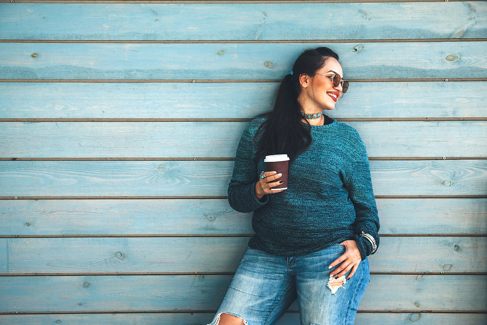 Beautiful woman wearing fall sweater, ripped jeans and glasses drinking take away coffee standing ag