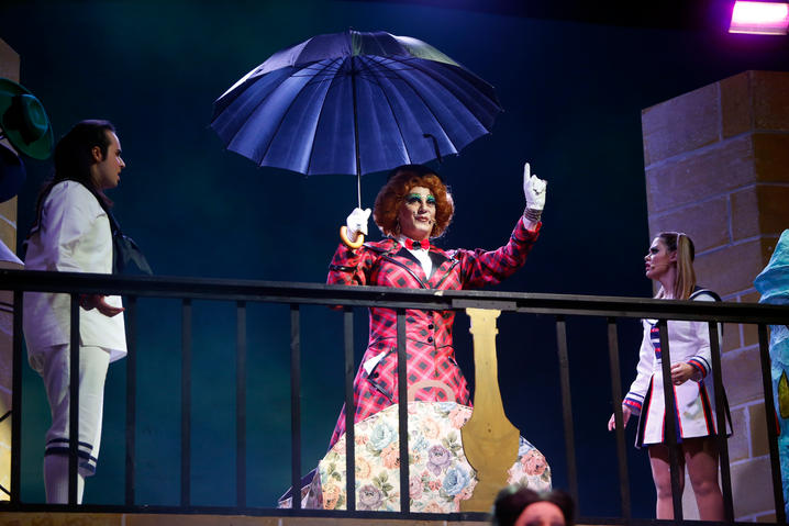 Merry Poppins (Alan Montanaro) makes her grand entrance out of a carpet bag.