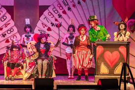 The Mad Hatter (Stephen Oliver) presents his case to the Queen and King of Hearts (Katherine Brown & Daryl Ebejer).