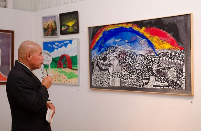 Minister of Social Cohesion, Dr. Norton reflects on a painting at the Guyana Visual Arts Competition and Exhibition (GVACE) Castellani House (Guyana Chronicle, 2019)