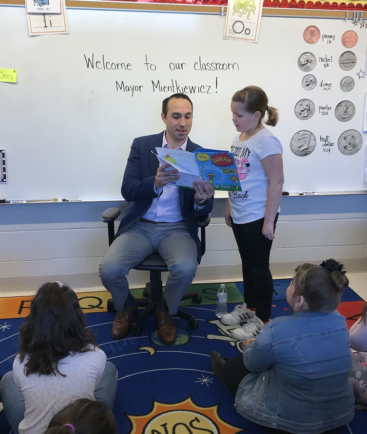 Mayor and student reading aloud