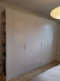 sprayed master wardrobe with a bookcase attached to the end