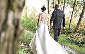 Paarfoto: Brautpaar schlendert Hand in Hand über einen kleinen Waldweg von der Kamera weg. . Copyright: Kornis, euer Hochzeitsfotograf aus dem Bezirk Wiener Neustadt