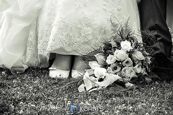 Nahaufnahme und Detailfoto in Schwarz-Weiß: Die unter dem spitzenbesetzten Brautkleid hervorlugenden Schuhe der Braut und die des Bräutigams sowie der im Gras liegende Brautstrauß. . Copyright: Kornis, euer Hochzeitsfotograf aus dem Bezirk Wiener Neustadt