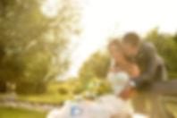 Paarfoto: Die Braut sitzt auf einer Bank im Grünen, sie hält den Brautstrauß im Schoß, der Bräutigam umarmt sie von hinten. Durch die Bäume im Hintergrund fällt das Licht der untergehenden Sonne. . Copyright: Kornis, euer Hochzeitsfotograf aus dem Bezirk Wiener Neustadt
