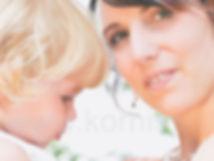 Nahaufnahme: Die Braut hält ihr kleines Kind im Arm und lächelt in die Kamera. . Copyright: Kornis, euer Hochzeitsfotograf aus dem Bezirk Wiener Neustadt