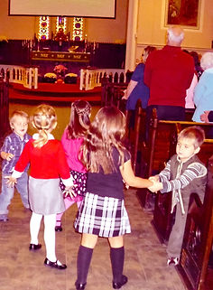 Children dance in the aisles during a popular upbeat closing hymn.
