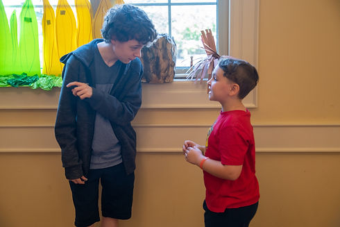 A young boy asks a question of a teen volunteer at a summer VBS at St. John's Church, Thorold.