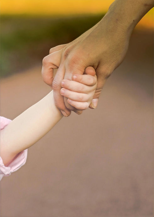 An older hand holds that of a young child.