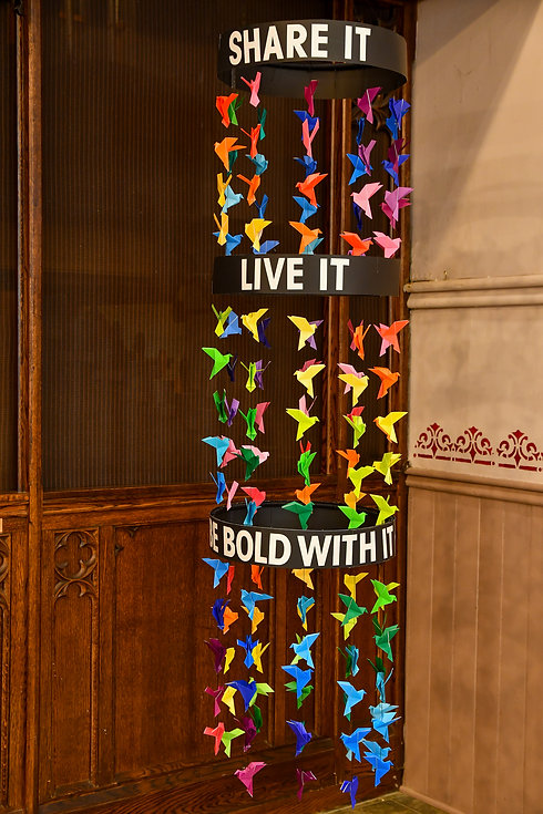 Multi-coloured origami paper doves hang from a mobile with the words Share it, Live it, Be Bold with it.
