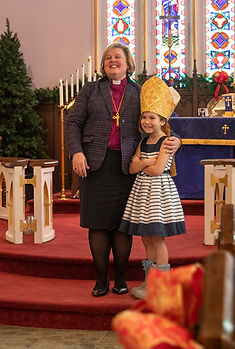 Bishop Susan Bell, Bishop of the Anglican Diocese of Niagara, teaches a very happy-to-learn young parishioner at St. John's Church, Thorold, about the clothing that a bishop wears.