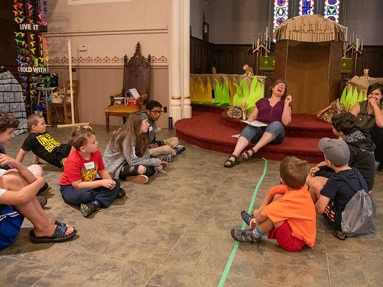 Canon Kathy, teen volunteer and children share a laugh at VBS at VBS at St. John's Church, Thorold.