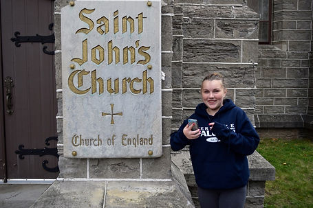 Young teenage girl standing by church sign, smiles as she looks up from cell phone.