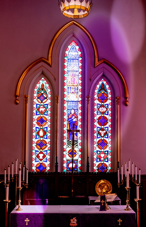 Trinity lancet windows with crown hanging above glow purple for lent at St. John's Church, Thorold.