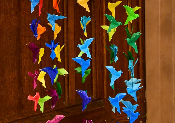 A close-up of paper origami doves that hang at the front of the church sanctuary.