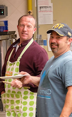 Two men work the griddle at a Shrove (Pancake) Tuesday community meal.